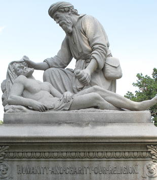 A stone plinth holds a sculptural group of two stone, male figures. One concerned-looking robed man crouches down to adjust the cloths on the head of a supine male figure. The lying man has a bare chest and a pained expression.