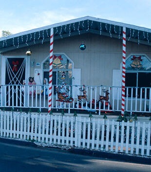 One of the cabins at a trailer park is decorated for christmas. Red ribbon is twirled around its posts, lights hang from the eaves, and plaster nativity figures sit on the porch.