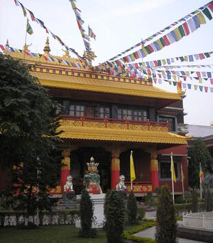 A gold and red Buddhist temple displays multiple ornamental roof tiers with golden eaves, red columns, and a porch on the second level. Lines of fabric flags are attached to the temple's golden roof, which is decorated with finials.