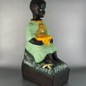 """A plaster figurine depicts a seated dark-skinned young boy in light green dress. It functions as a coinbox via a slot in a basket held by the figure. A banner above the basket reads, """"MERCI."""" It has been painted over another inscription """"THANK YOU."""""""