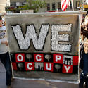 "Two light-skinned men hold up a banner at a protest. It reads, ""WE OCCUPY."" The letters of WE are filled with sillhouettes of protesters. The letters of OCCUPY are checkered and interspersed with photos of Manhattan and nuclear explosions."